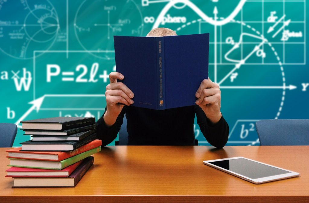 Professional clutching book in front of blackboard